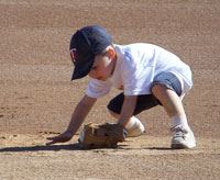 Child Playing in Dirt with Baseball Glove